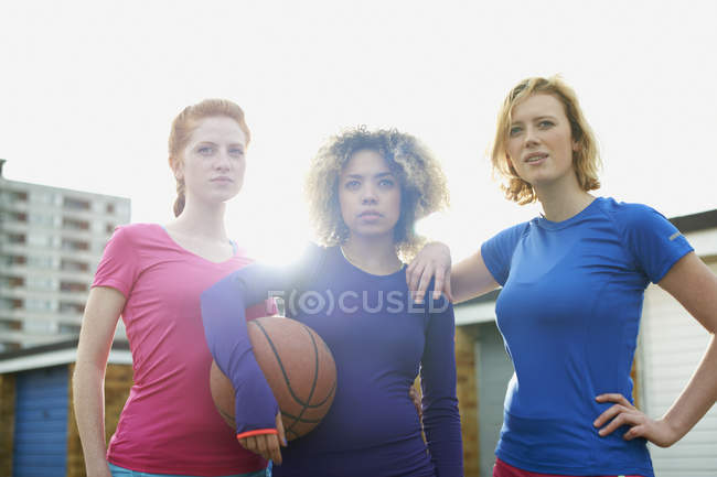 Portrait de trois femmes exerçant ensemble tenant un ballon de basket — Photo de stock