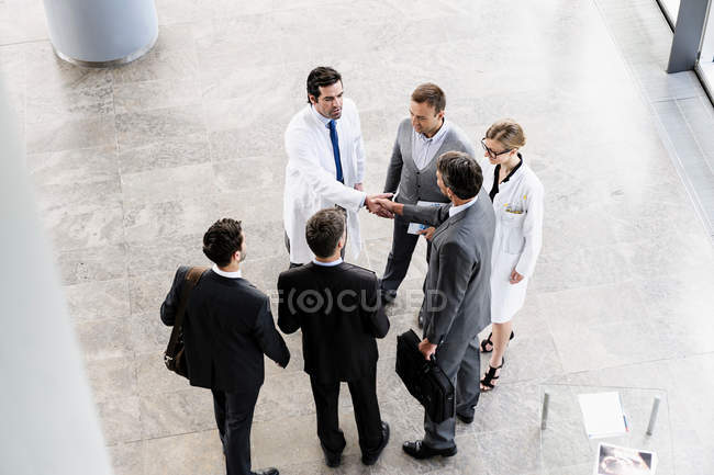 Business people and doctors greeting — Stock Photo