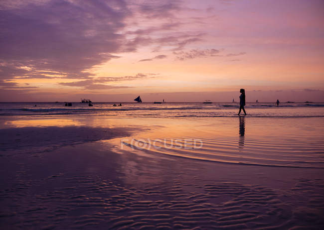 Silhouetted young woman on beach at sunset, Boracay Island, Visayas, Philippines — Stock Photo