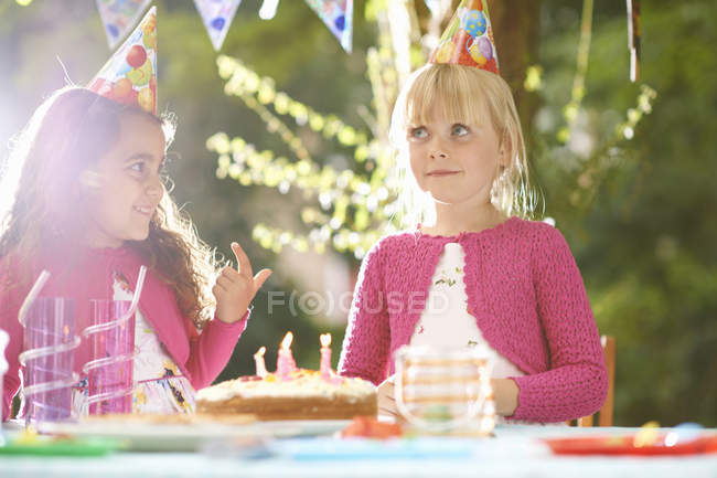 Girls with finger in birthday cake at  garden birthday party — Stock Photo