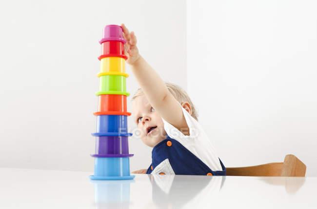 Ragazzino giocare con impilamento tazze — Foto stock