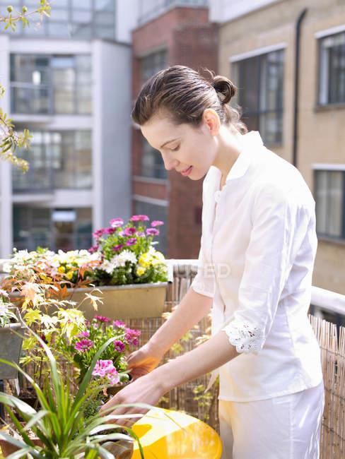 Жінка на балконі з квітами — стокове фото