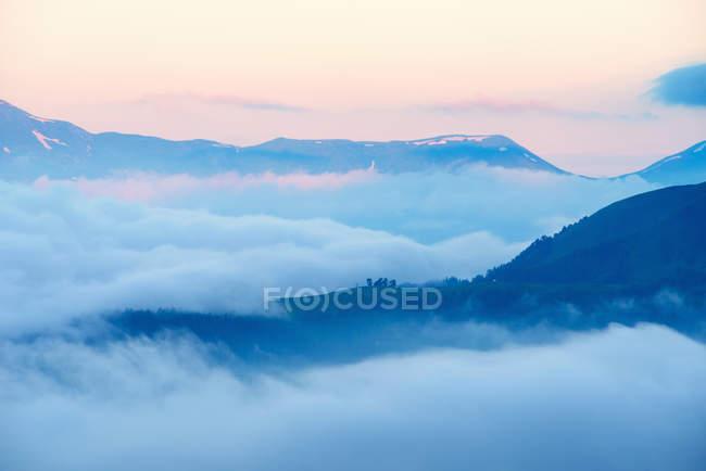 Vista de las montañas por encima de las nubes al amanecer - foto de stock