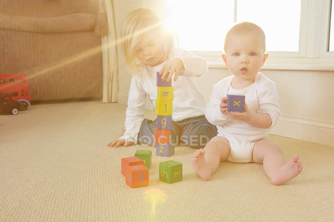 Children playing with toys on floor — Stock Photo