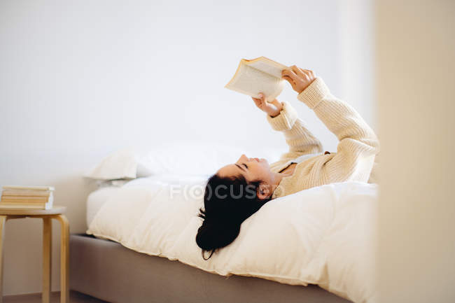 Young woman lying on bed reading book — Stock Photo