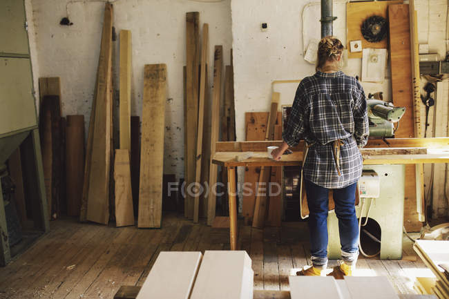 Young craftswoman at workbench in pipe organ workshop — Stock Photo
