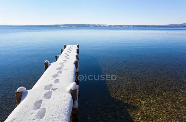 Следы на снегу крытый пирс — стоковое фото
