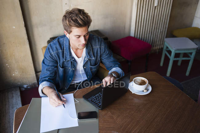 Young male student sitting at cafe table typing on laptop — Stock Photo