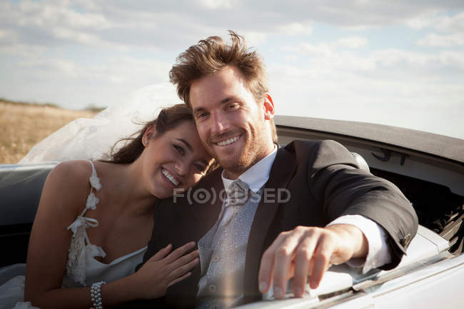 Newlywed couple riding in convertible — Stock Photo