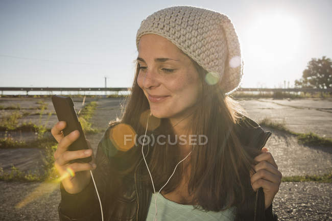 Young woman wearing earphones listening to music — Stock Photo