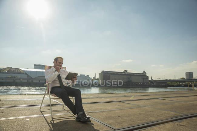 Homme d'affaires assis sur une chaise sur des rails de tramway en utilisant une tablette — Photo de stock