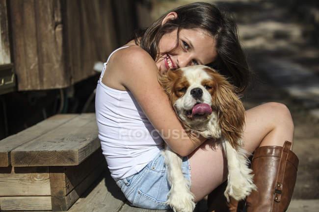 Портрет улыбающейся девушки, обнимающей собаку на ступеньках — стоковое фото
