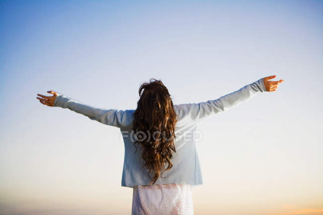 Rear view of woman standing with arms outstretched — Stock Photo