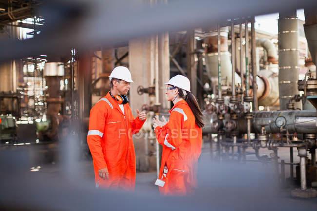 Робітники, які розмовляють на нафтопереробному заводі — стокове фото