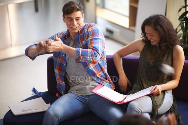 Giovane allievo maschio gettando carta sgualcita in sala comune — Foto stock