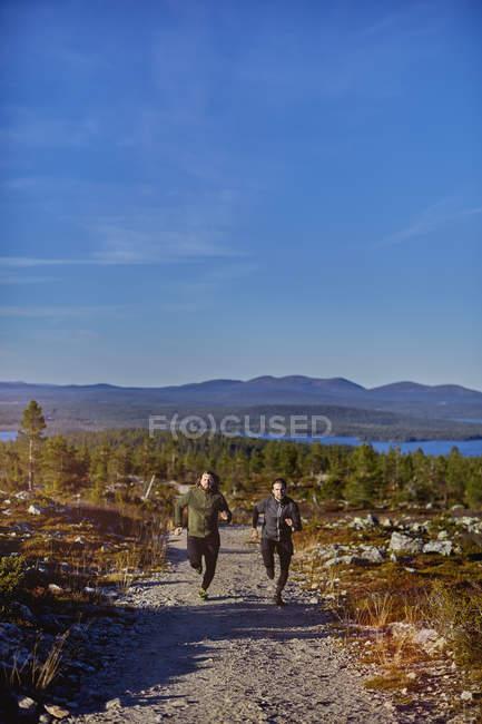 Sentier d'hommes fonctionnant sur la route de gravier, Sarkitunturi, Laponie, Finlande — Photo de stock