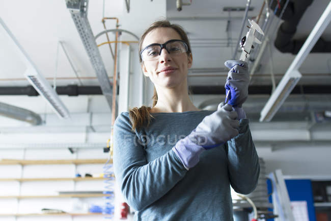 Low angle view of woman in workshop wearing safety goggles holding tool — Stock Photo