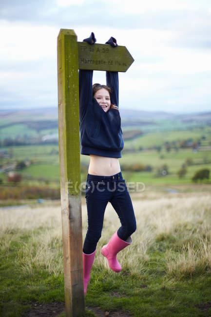 Smiling girl climbing road sign — Stock Photo