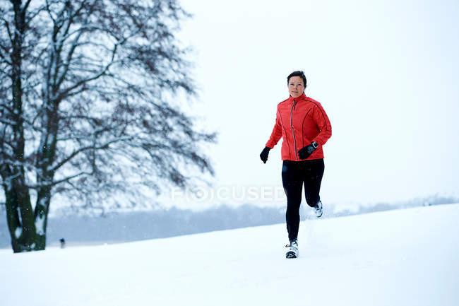 Mulher correndo na floresta de inverno — Fotografia de Stock