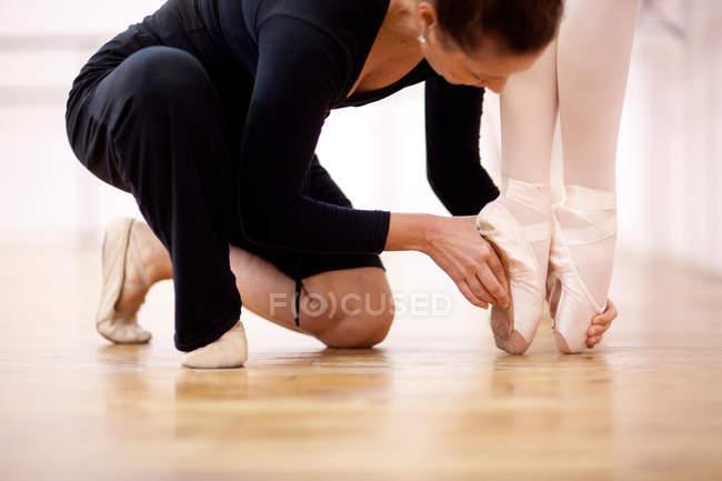 Teacher adjusting foot position of ballerina — Stock Photo