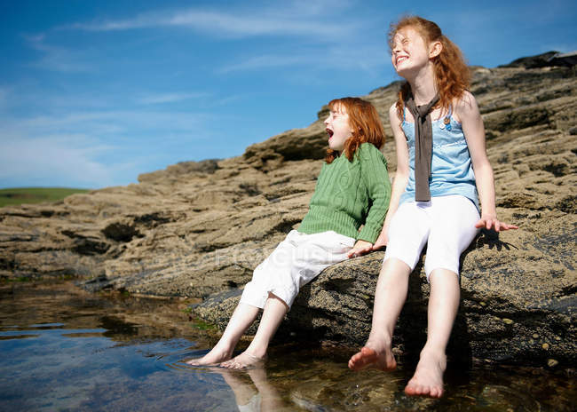 2 girls putting feet in cold rock pool — Stock Photo