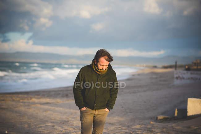 Uomo di mezza età sulla spiaggia tempestosa, Sorso, Sassari, Sardegna, Italia — Foto stock