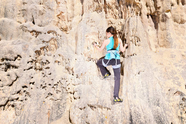 Teenage rock climber on rock face — Stock Photo