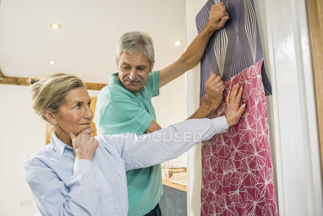 Senior couple making decision on wallpaper — Stock Photo