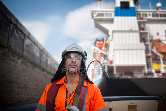 Portrait of tug worker wearing hard hat and protective goggles holding tool — Stock Photo