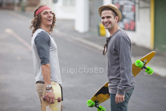 Portrait of two male adult friends with skateboards on city street — Stock Photo