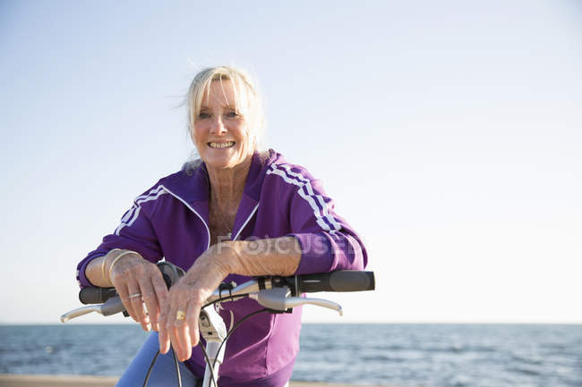 Senior woman on bicycle by beach — Stock Photo