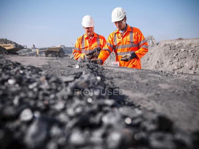 Exploitants charbonniers inspectant le charbon dans une colamine à ciel ouvert — Photo de stock