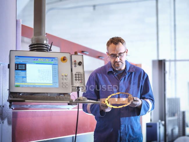 Ingénieur tenant composant de découpe laser dans l'usine d'ingénierie — Photo de stock