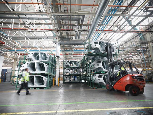 Автозапчасти на автомобильном заводе и размытые лица — стоковое фото