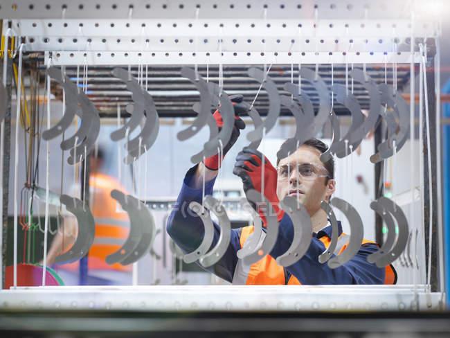 Arbeiter arrangiert Metallteile für das Spritzen von Farbe in der Blechfabrik — Stockfoto