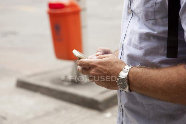 Primer plano de los mensajes de texto del hombre en el teléfono inteligente, ciudad de Copacabana, Río de Janeiro, Brasil - foto de stock