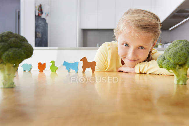 Дівчина грає з іграшковими тваринами навколо брокколі — стокове фото