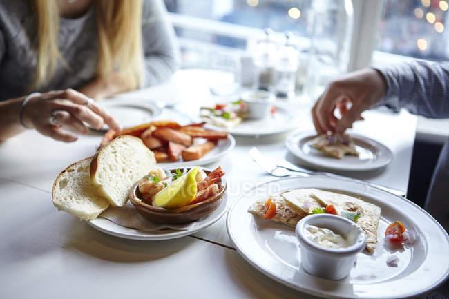 Aufnahme der jungen Paare Hände Finger Essen im Café beschnitten — Stockfoto