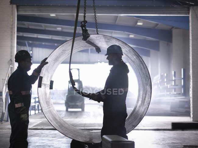 Ingénieurs utilisant la grue pour soulever de gros tubes en acier dans l'usine d'ingénierie — Photo de stock