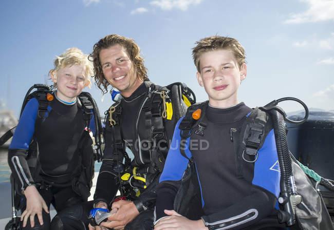 Портрет двух мальчиков с учителем подводного плавания среднего возраста — стоковое фото