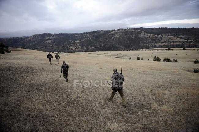 Чотири оленя мисливці ходьба по полю, Джон день, Орегон, США — стокове фото
