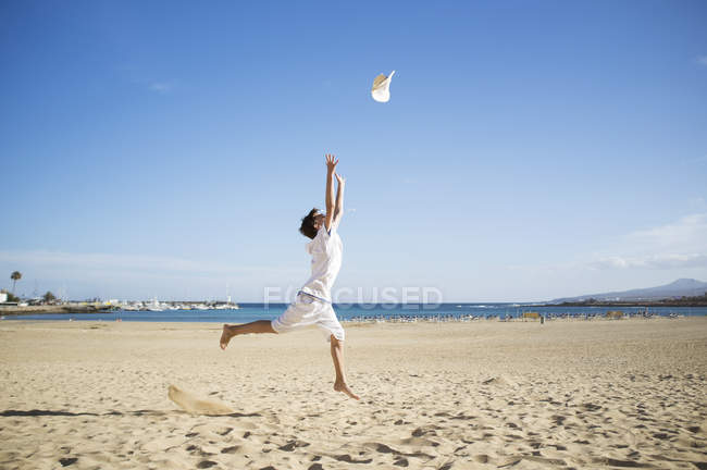 Boy jumping and throwing hat mid air on beach — Stock Photo