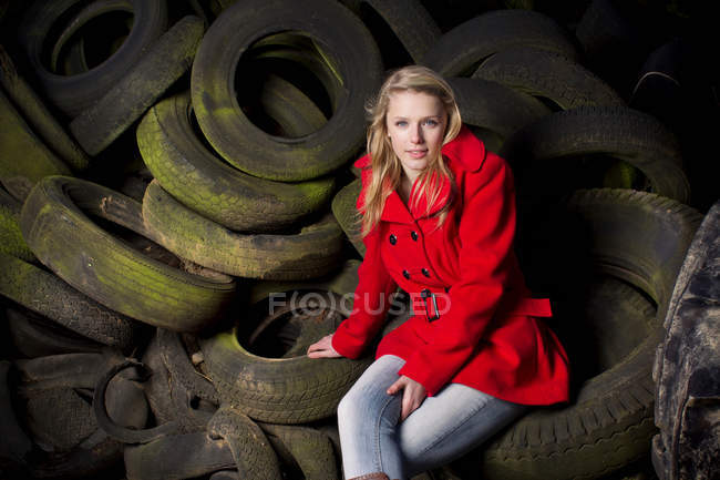 Teenage girl sitting on discarded tires — Stock Photo