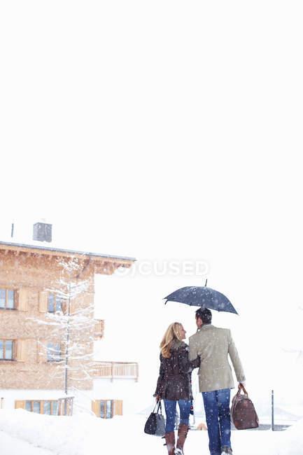 Pareja caminando juntos en la nieve — Stock Photo