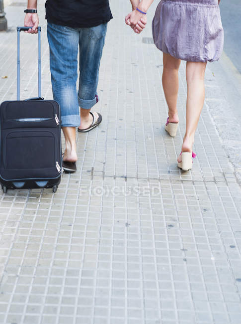 Cropped shot couple with trolly walking along street — Stock Photo