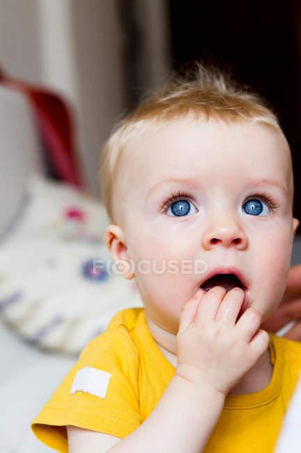 Ребенок жует пальцы, фокусируясь на переднем плане — стоковое фото