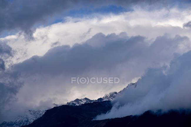 Wolken über schneebedeckten Berghang — Stockfoto