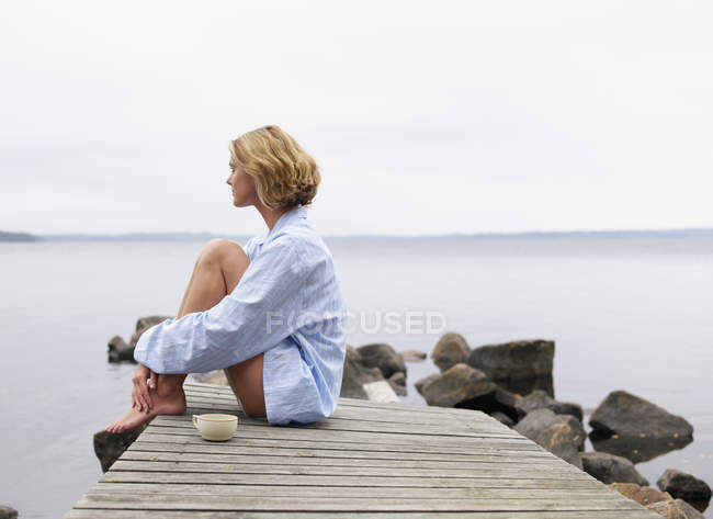 Woman with eyes closed sitting on a dock — Stock Photo