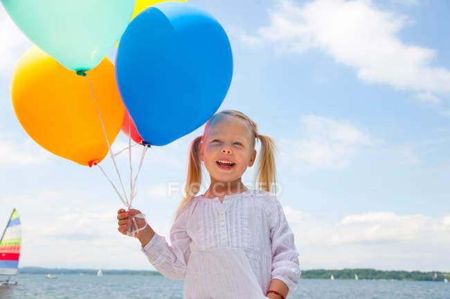 Menina segurando monte de balões ao ar livre — Fotografia de Stock