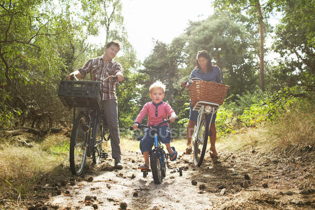 Family cycling though forest — Stock Photo